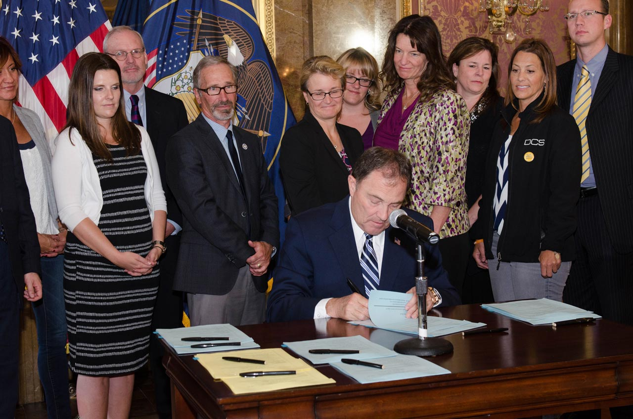 Utah Gov. Gary Herbert ceremoniously signed into law five bills related to the problem of suicide in Utah, while government administrators and citizens who have survived a suicide loss look on.